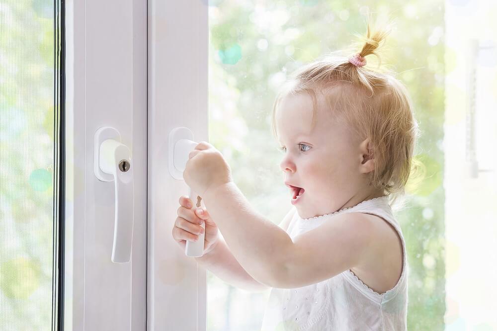 niña abriendo ventana. Seguridad infantil en el hogar.
