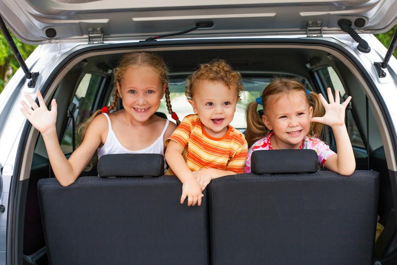 tres niños en un coche